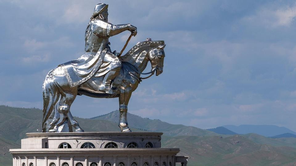 Une statue argentée de Genghis Khan sur un cheval.