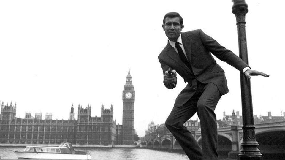 L'acteur se tient debout au bord de la Tamise avec la tour de Big Ben en arrière-plan et il s'apprête à tirer avec un revolver.