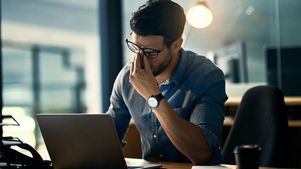 Un travailleur est stressé à son poste de travail.