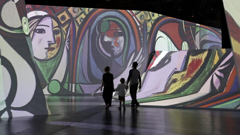 Un homme, une femme et un enfant se promènent dans l'exposition, entourés d'œuvres de Picasso projetées sur les murs.