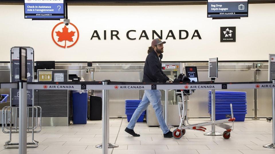 Un homme qui pousse un panier marche devant un comptoir d'enregistrement d'Air Canada dans un aéroport.