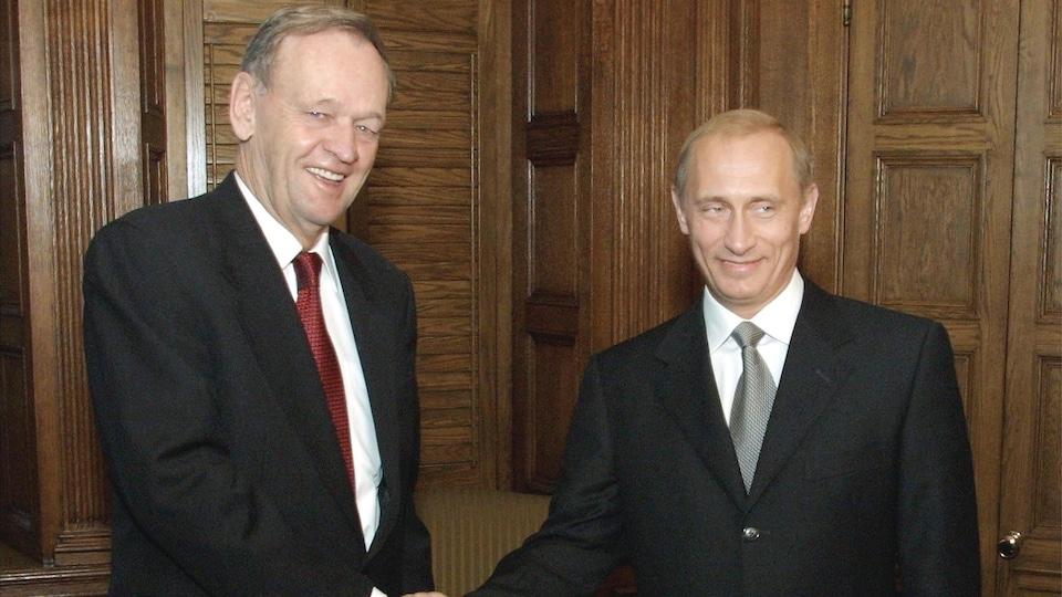 L'ancien premier ministre du Canada Jean Chrétien et l'actuel président russe Vladimir Poutine se serrent la main.