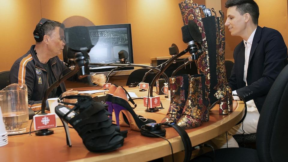 Dans un studio de radio, un animateur parle à un homme. Des chaussures pour femmes se trouvent sur la table.