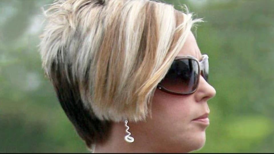 Femme aux cheveux blonds, portant des verres fumés et une coupe de cheveux asymétriques, vue de profil.
