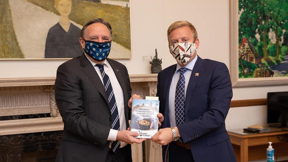 Le premier ministre François Legault et le député Mathieu Lévesque tiennent un exemplaire du livre <i>Les recettes des parlementaires de l'Assemblée nationale du Québec</i>.