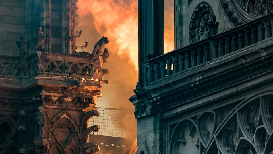 Les flammes et la fumée sont visibles près des gargouilles décorant le toit et les flancs de la cathédrale Notre-Dame de Paris.