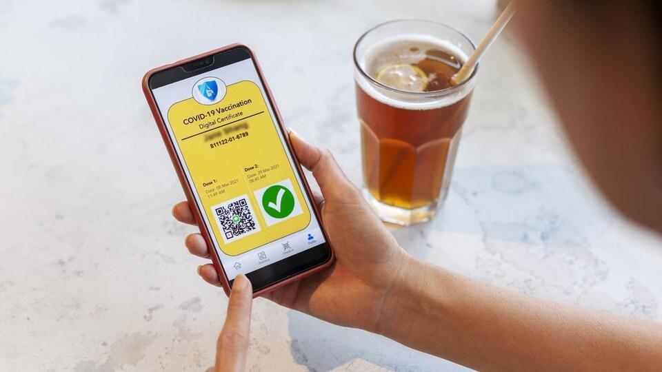 Une femme au restaurant affiche un code QR sur l'écran de son téléphone qui certifie sa vaccination contre la COVID-19.