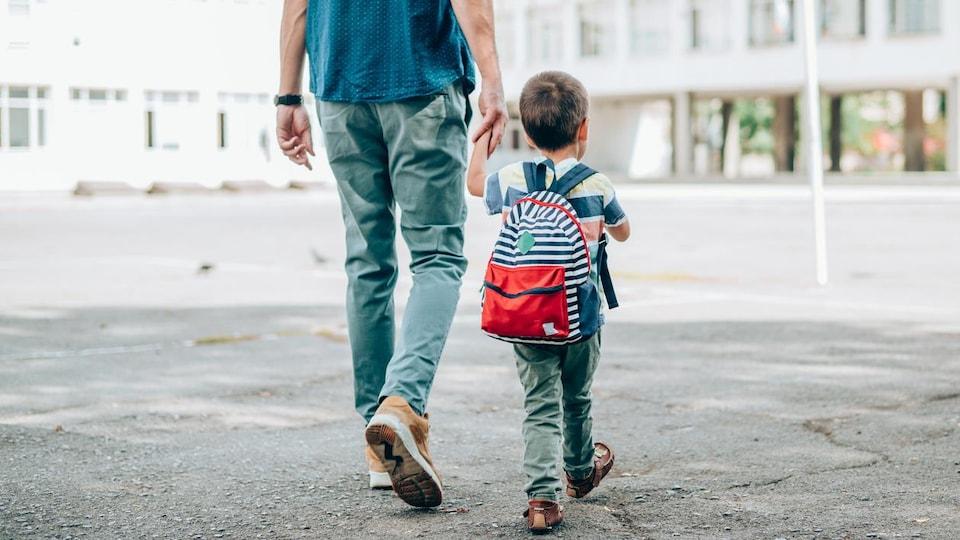 Un homme tient un jeune enfant par la main dans une cour d'école.