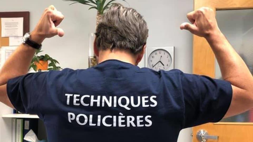 """Photo de lui de dos qui porte un chandail avec l'inscription """"Techniques policières""""."""