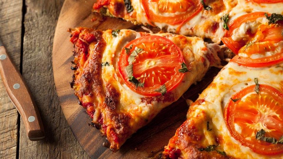 Gros plan sur une part de pizza à la tomate et au fromage.