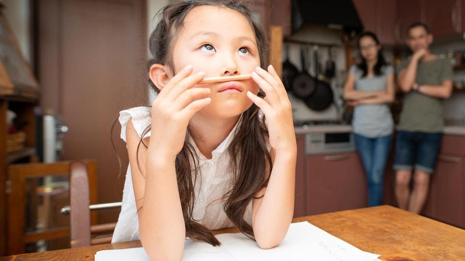 Une fillette attablée joue avec son crayon au lieu d'étudier
