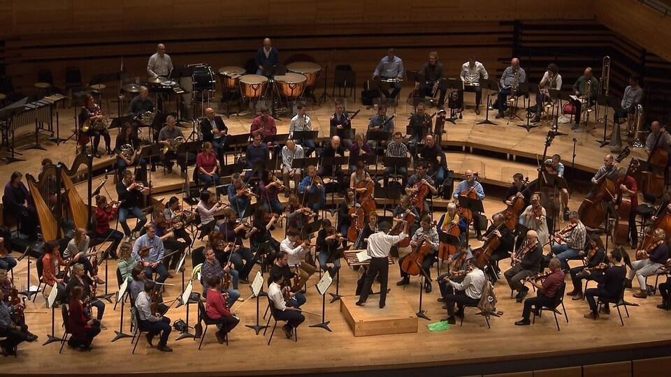 On voit, en plongée depuis un balcon, Kent Nagano et les membres de l'OSM en pleine répétition à la Maison symphonique de Montréal.