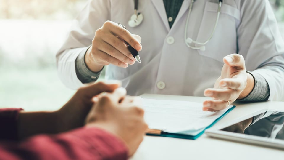Un médecin et sa patiente discutent, assis à un bureau.