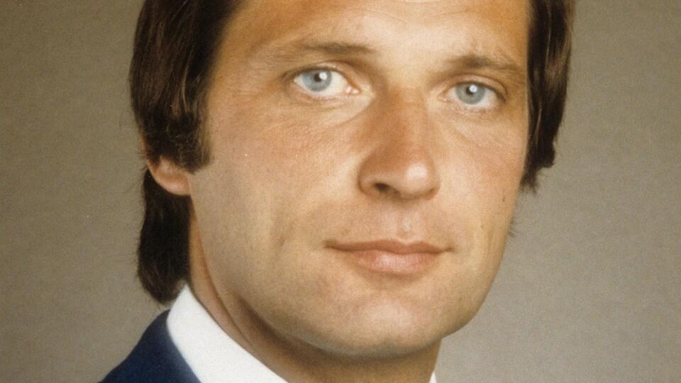 Un homme portant un veston et une cravate pose en regardant la caméra.
