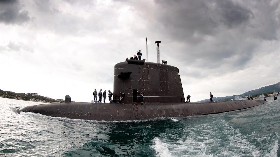 Un sous-marin émerge de l'eau avec des hommes sur le pont.