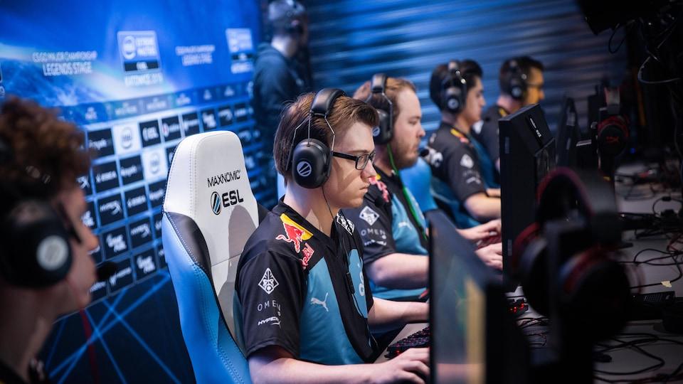Un athlète de esports est assis devant un écran d'ordinateur lors d'un match du jeu Counter Strike : Global Offensive.