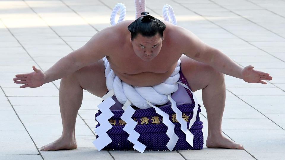 Un lutteur de sumo fait une sorte de salut en ouvrant ses bras.