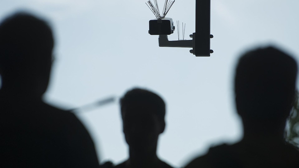 Une  caméra est fixée dans les airs alors que des passants, en contrejour, circulent.