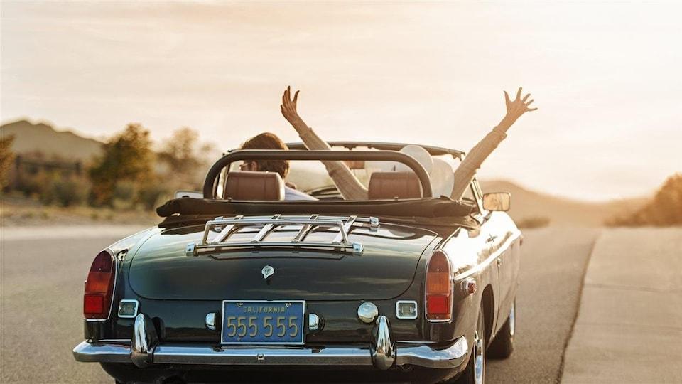 Un homme et une femme roulent dans une décapotable.