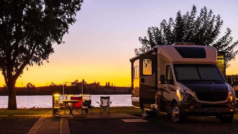 Photo prise au coucher du soleil d'une véhicule récréatif stationné au bord d'un plan d'eau avec des chaises et une table de camping sorties.