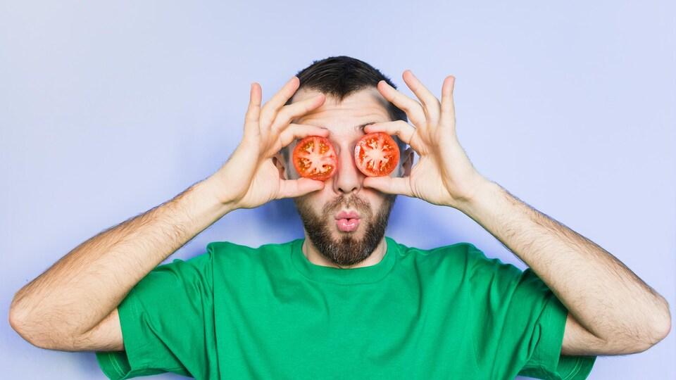 Un jeune homme tient des rondelles de tomates devant ses yeux.