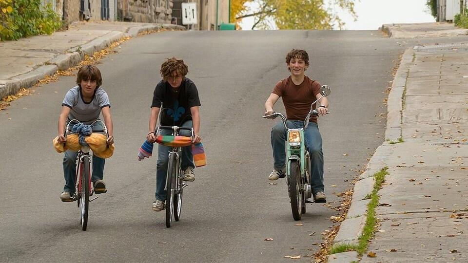 Trois garçon font du vélo.