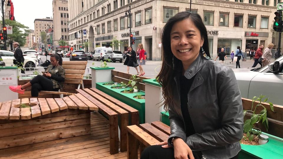 Mme Wong assise sur un banc, en bordure de la rue Sainte-Catherine Ouest, à Montréal.
