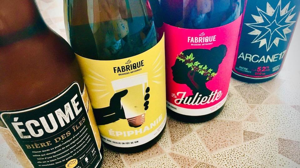 Quatre grosses  bouteilles de bière alignées .