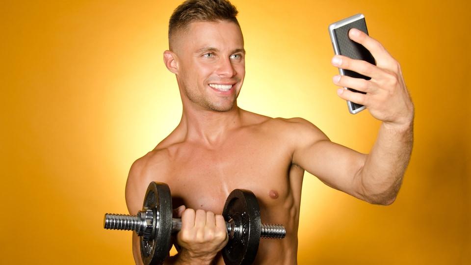 Un jeune homme séduisant, torse nu, tient un poids d'entraînement de sa main droite pendant qu'il se prend en égoportrait avec son portable de la main gauche.