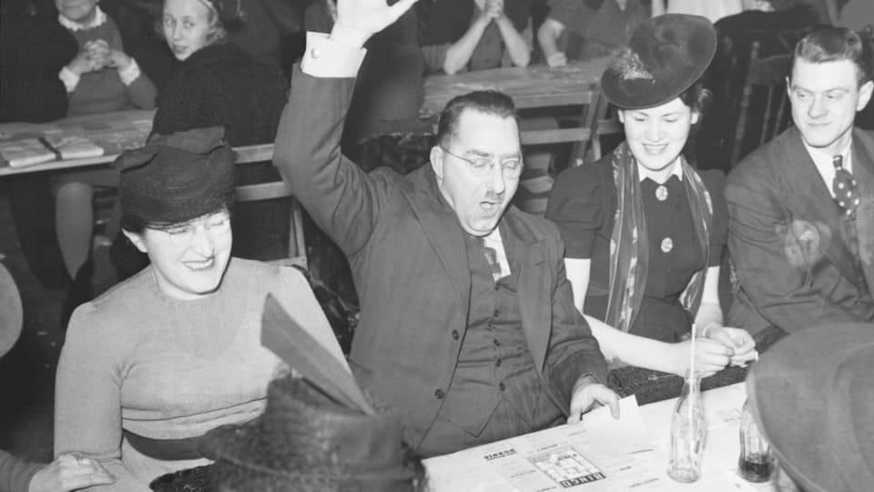 Un gagnant de bingo, assis avec d'autres joueurs, lève la main. Cette partie a lieu au 4555, avenue Notre-Dame-de-Grâce à Montréal en 1941.