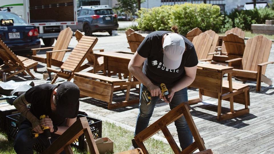 Deux hommes construisent des bancs publics dans une place urbaine.
