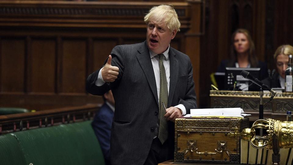 Le premier ministre de Grande-Bretagne, Boris Johnson, debout à la Chambre des communes, lève le pouce en signe d'approbation.