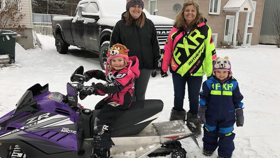 Une famille composée de grand-maman, mère et deux fillettes portent leurs bottes de poil et se font prendre en photo avec une petite motoneige.
