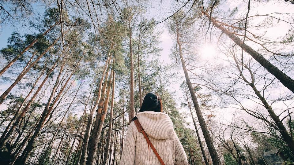 De dos, une femme regarde le ciel dans une forêt.
