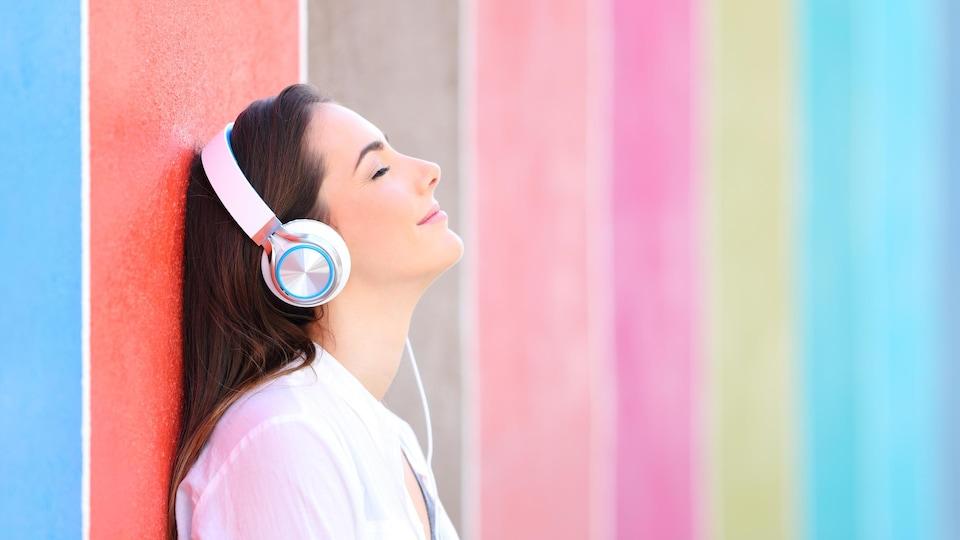 Une femme sourit en écoutant de la musique.