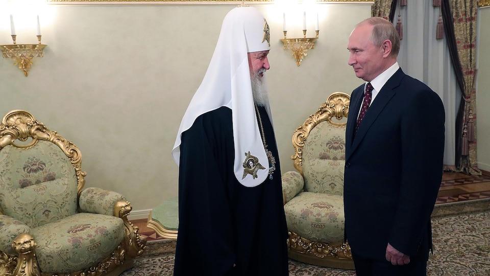 Un homme vêtu d'un costume religieux orthodoxe parle à un homme en veston cravate.