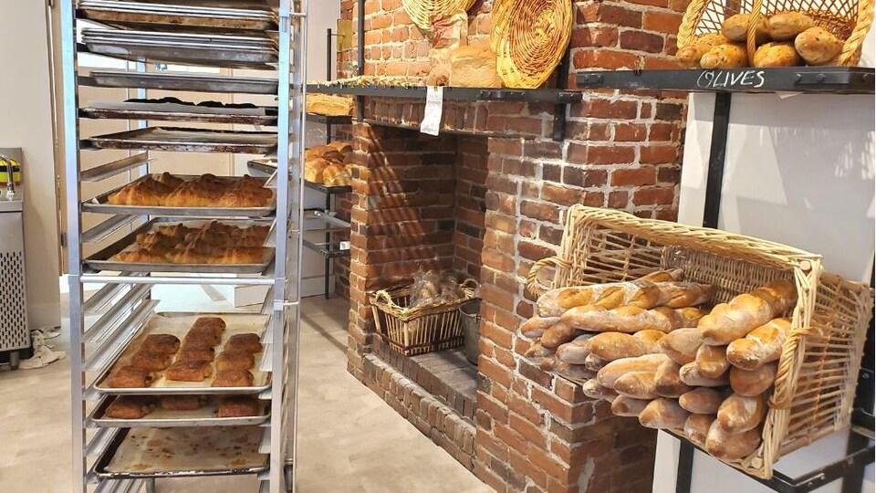 L'intérieur de la boulangerie Louis-Marchand et Compagnie où l'on retrouve des croissants et des pains au chocolat sur des plaques de cuisson, des baguettes dans un panier en osier et des pains de fesse sur une étagère de part et d'autre d'une cheminée en briques.