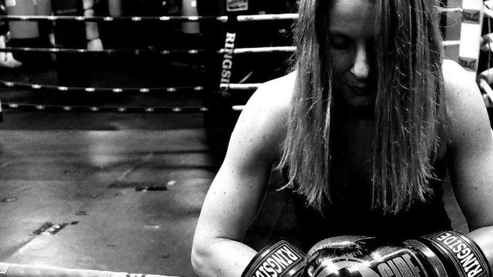 Rachelle Thibodeau, boxeuse et entraîneuse à Pan Am Boxing Club, se tient contre les cordes du ring de la salle de boxe Pan Am Boxing Club, portant ses gants