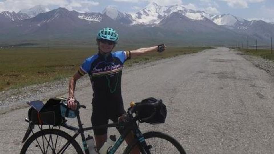 Brenda Trentholme a une main sur le sièege de son vélo et elle pointe les montagnes enneigées en arrière-plan avec son autre main.