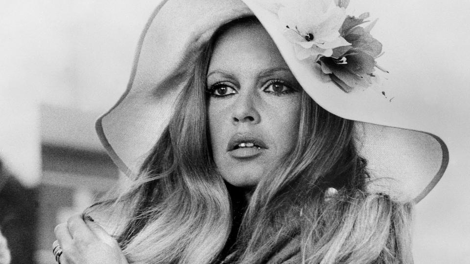 Portrait de l'actrice portant un grand chapeau et se passant les mains dans les cheveux.