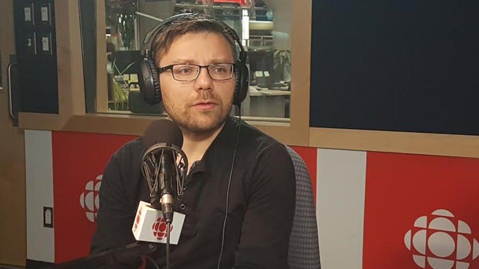 Un homme est assis devant un micro dans un studio de radio.