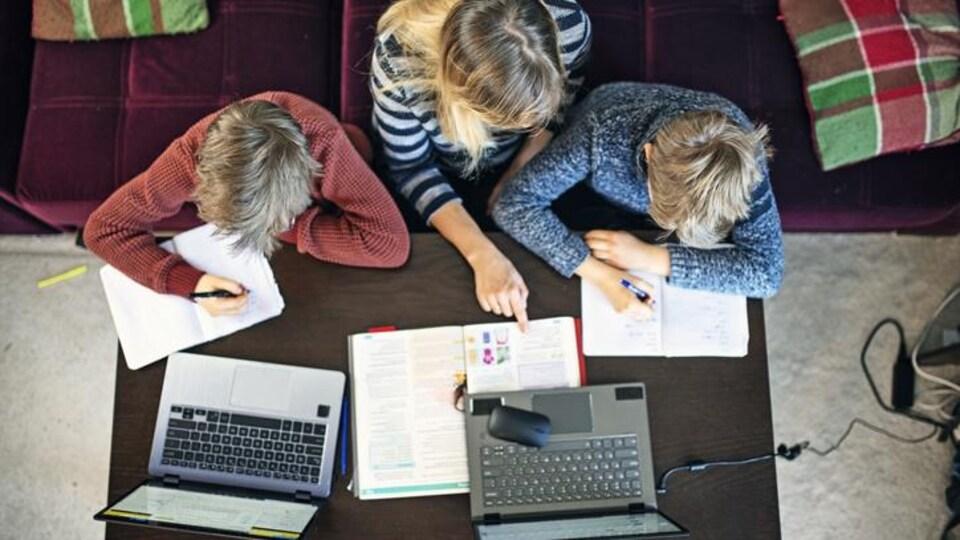 Une femme aide un enfant à faire des devoirs.