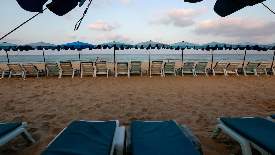 Des chaises longues vides sur une plage déserte.