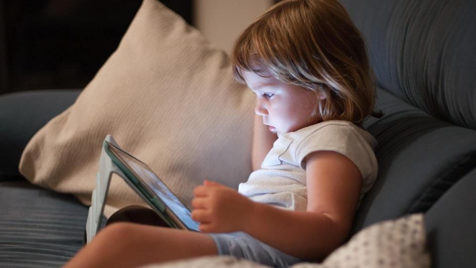 Une jeune enfant assise sur un canapé en train de regarder l'écran d'une tablette électronique.