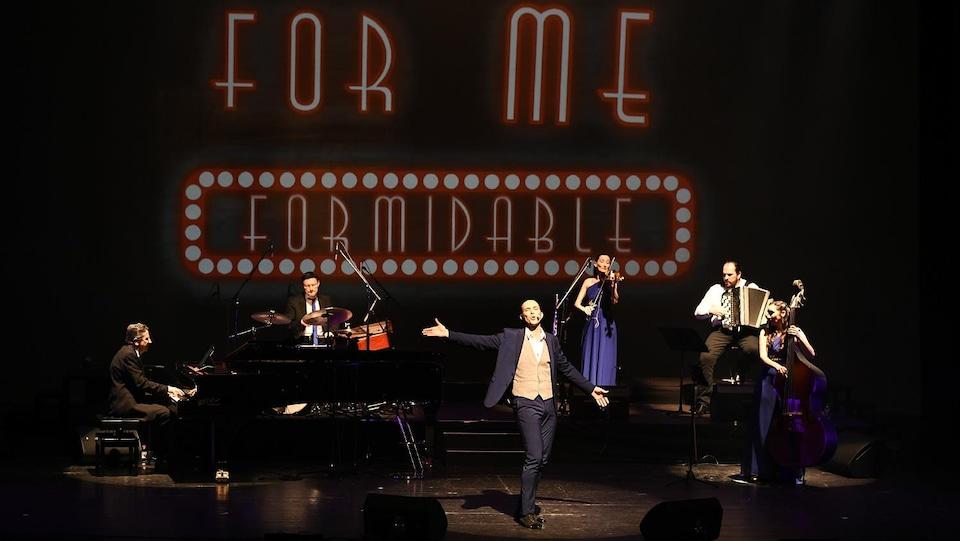 Scène du spectacle avec les musiciens et le chanteur sur une scène, avec le titre For me formidable en néon en décor.