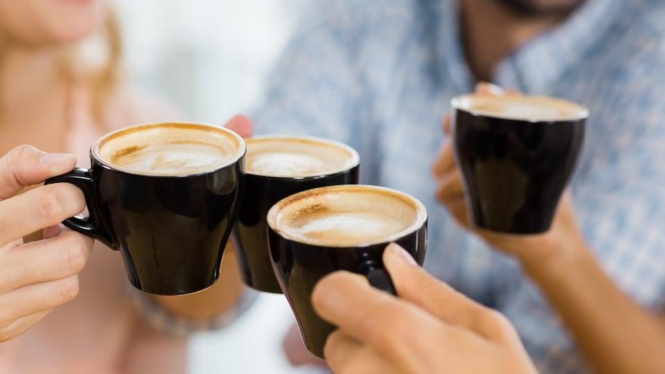 Plusieurs personnes font un toast avec des tasses de café