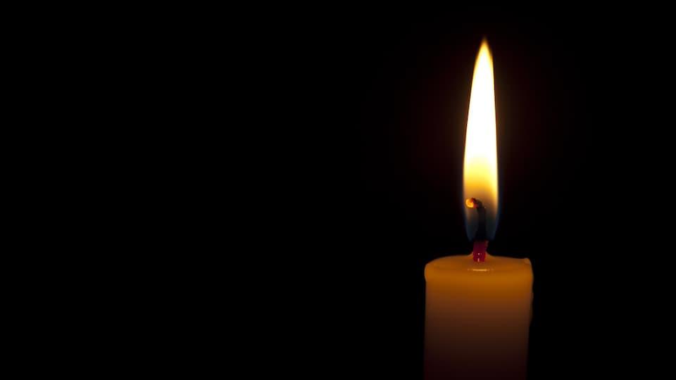 Une chandelle illumine une pièce dans le noir.
