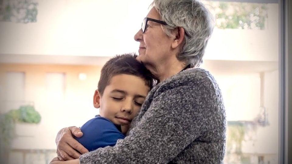 Un jeune garçon se fait prendre dans les bras de sa grand-mère.