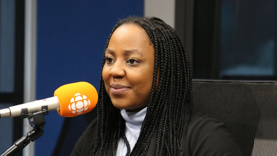 Une femme se tient devant le micro en souriant.
