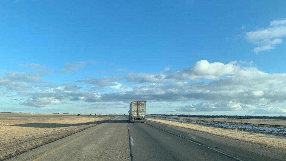 Un semi-remorque sur une autoroute au milieu des Prairies.